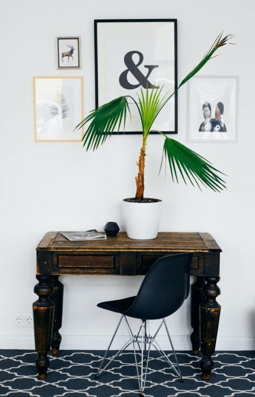 Dunkelbrauner Holztisch mit Fotowand darüber
