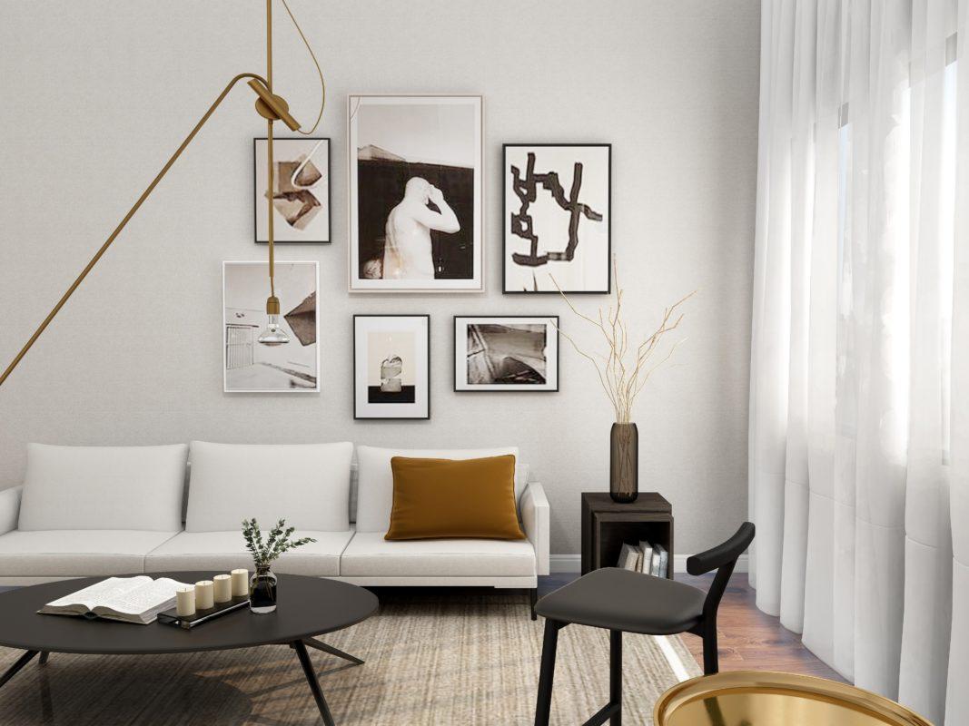 Helle Wohnzimmeratmosphäre mit zurückhaltenden Farben. Im Fokus steht eine helle Couch mit einem rostfarbigen Kissen. Vor der Couch steht ein schwarzer Couchtisch sowie ein dunkler Holzstuhl. Oberhalb der Couch ragt eine Hängeleuchte von der Decke und befindet sich eine Bilderwand