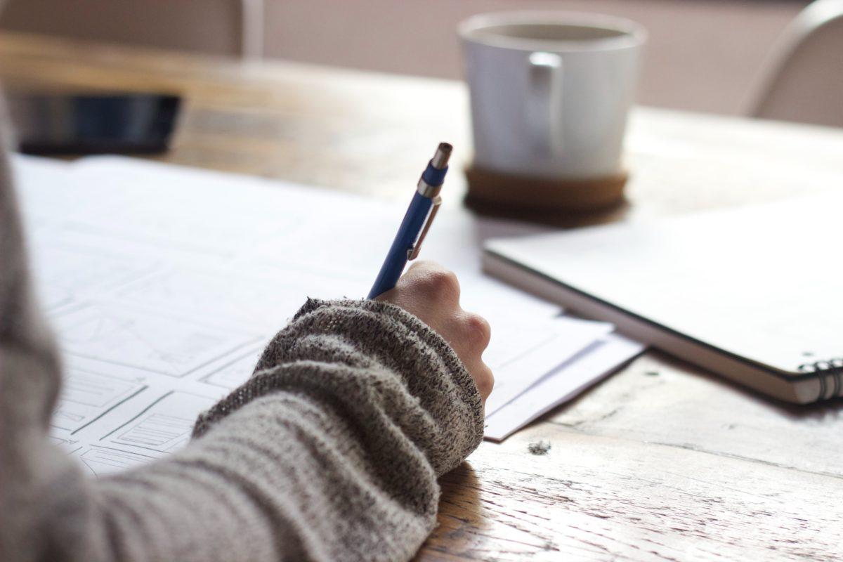 Frauenhand schreibt mit dunkelblauem Kugelschreiber auf ein weißes Blatt Papier. Im Hintergrund steht eine weiße Kaffeetasse