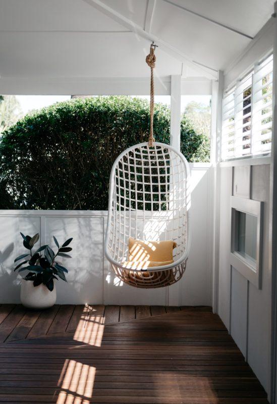Weißer Korbsessel aus Rattan hängt von der Decke auf überdachter Terrasse