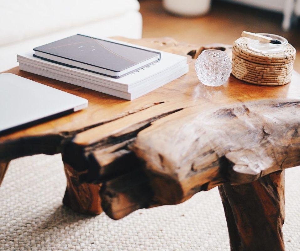 Massiver, mittelbrauner Couchtisch aus Holz steht auf einem weißen Teppich.Auf dem Tisch liegen Bücher und ein Laptop sowie ein Windlicht aus Glas.